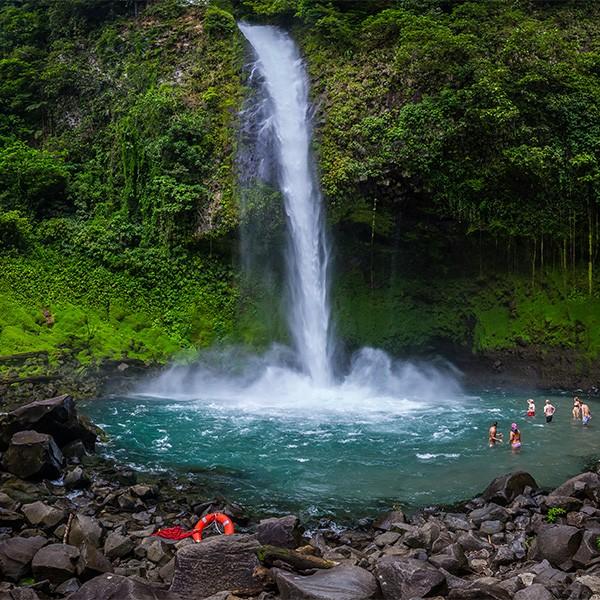 Niños bañándose en la piscina natural al pie de la catarata de la Fortuna, Costa Rica